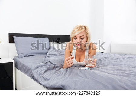 sick woman hold hand on head with pack of pills, young girl ill lying on bed at home - stock photo