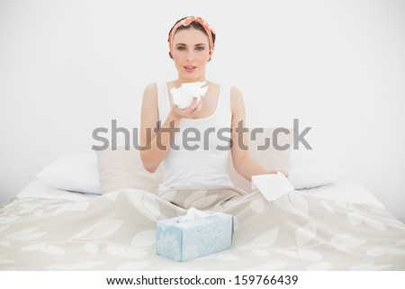 Sick woman holding a handkerchief sitting on her bed looking into the camera - stock photo