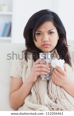 Sick woman holding a tissue and a glass of water in a living room - stock photo