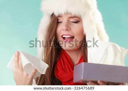 Sick woman in fur hat sneezing in tissue. Ill girl caught winter cold flu in studio on green.