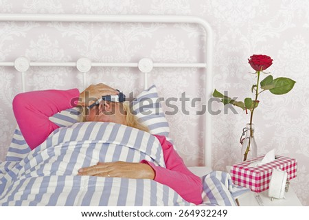 Sick woman in pink pajama with headache, tissues and a rose lying in bed with washcloth - stock photo