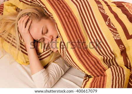 Sick woman lying in bed covered with blanket, feeling ill, has flu, fever and cough. - stock photo