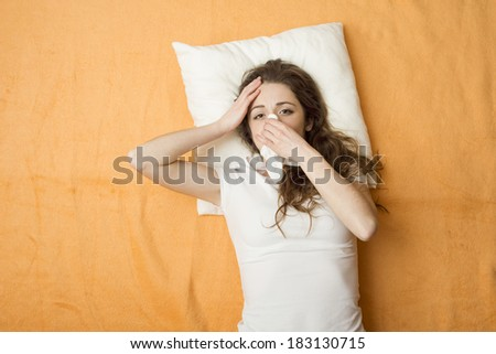 Sick woman lying in bed with cold and flu. She is blowing nose. She has a headache. - stock photo