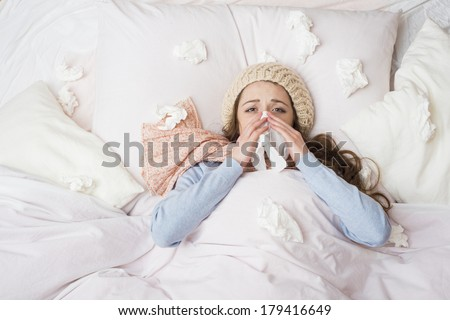 Sick woman lying in bed with high fever. She is blowing nose. - stock photo