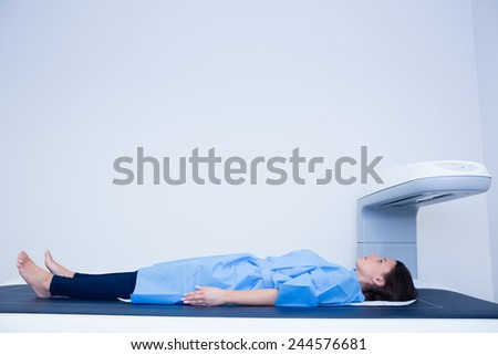 Sick woman lying on a x-ray machine in hospital - stock photo