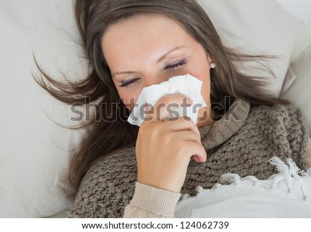 Sick woman lying on sofa and blowing nose in the living room - stock photo