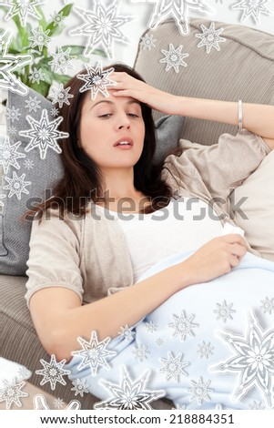 Sick woman lying on the sofa and touching her forehead against snowflakes - stock photo