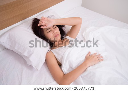 sick woman on bed concept of stomachache, headache, hangover, sleeplessness or insomnia - stock photo