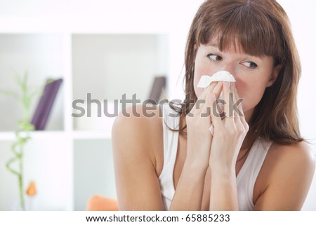 sick woman on sofa with handkerchief sneezing - stock photo