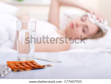 Sick woman resting in bed with focus to a glass of water and a blister pack of tablets and medication lying on the table alongside her bed