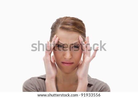Sick woman rubbing her temples against a white background