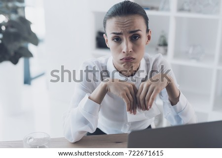 Sick woman sitting at her workplace in the office. She sits and holds a paper in her hands. She has a very unhappy face.