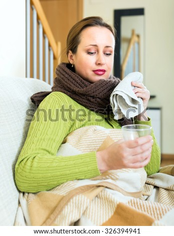 Sick woman sitting on a sofa under a blanket with a glass of warm drink