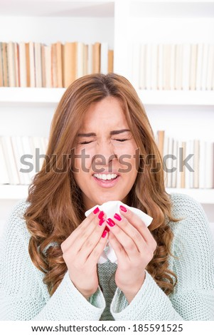 sick woman sniffles with flu virus feeling ill sneezing into tissue - stock photo
