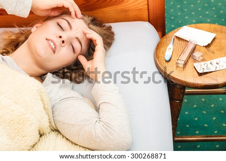 Sick woman suffering from headache pain. Ill girl laying in bed caught cold. Thermometer and pills on table. - stock photo