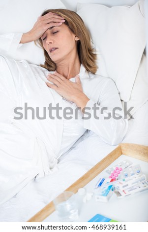 sick woman suffering in her bed with pills