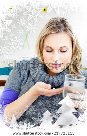 Sick woman taking pills holding a glass of water with christmas frame - stock photo