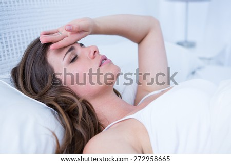Sick woman touching her forehead at home in the bedroom - stock photo
