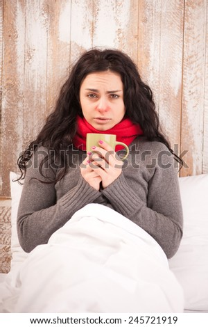 Sick woman with cup of tea. Closeup image of young frustrated woman in knitted scarf holding a cup of tea while sitting in bed against wooden wall - stock photo