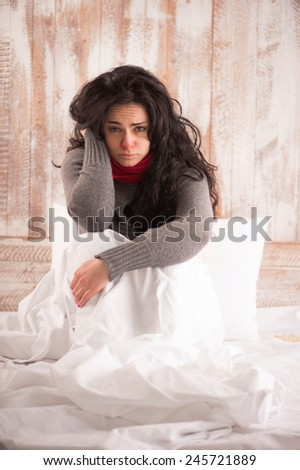 Sick woman with flu. Closeup image of young sick woman with scarf on her neck sitting in bed and holding her head in country house on the background - stock photo