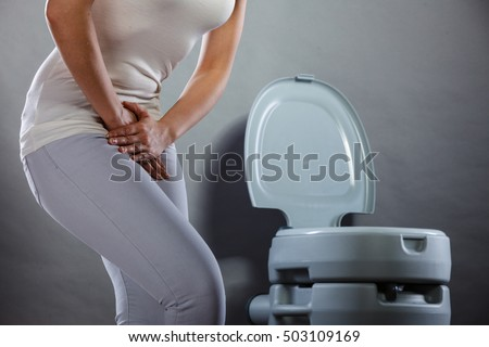 Sick woman with hands holding pressing her crotch lower abdomen in front of toilet bowl. Medical problems, incontinence, health care concept