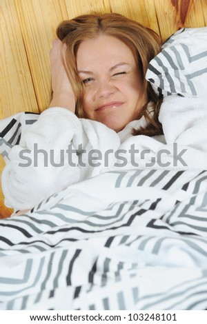 Sick woman with headache lying in the bed - stock photo