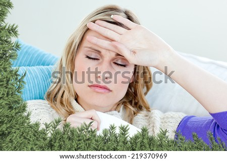 Sick woman with headache lying on the sofa in the livingroom against green fir branches - stock photo