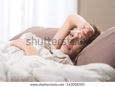 Sick woman with medical thermometer lying on bed - stock photo