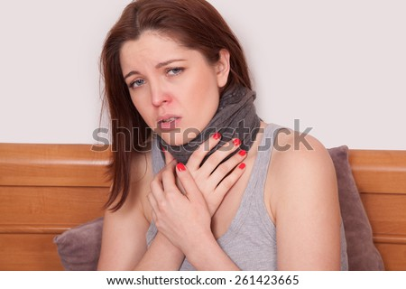 Sick woman with terrible sore throat. Closeup image of young woman with red nose in bed with thick scarf and touching her neck and head feeling pain - stock photo
