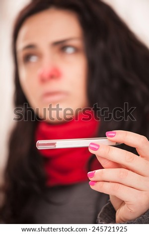 Sick woman with thermometer. Closeup image with selective focus on young frustrated woman in knitted scarf holding thermometer while sitting against wooden wall - stock photo