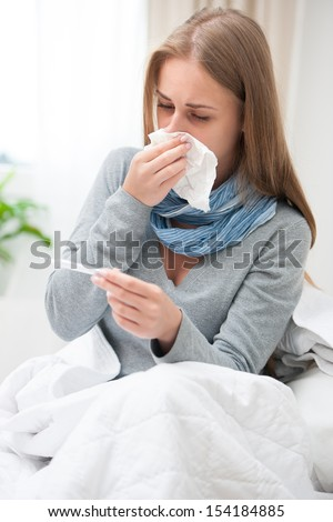 Sick woman with thermometer  in bed. Cold, flu, fever and migraine - stock photo