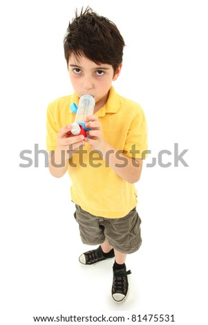 Sick young boy child using asthma inhaler with spacer chamber over white.  Has periorbital hyperpigmentation. - stock photo