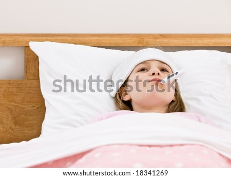 Sick young girl with fever having her temperature taken with thermometer while laying in bed