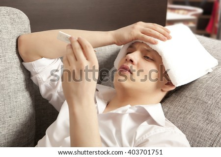 Sick young man lying on sofa checking his temperature at home in the living room