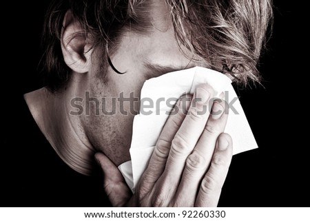 sick young man with handkerchief - stock photo