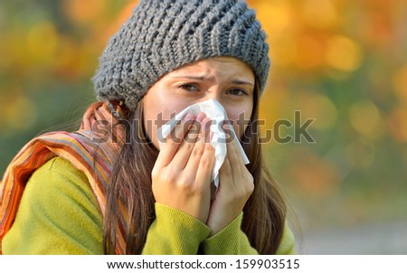 Sick young model isolated on autumn background blowing her nose