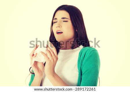Sick young woman blowing her nose - stock photo