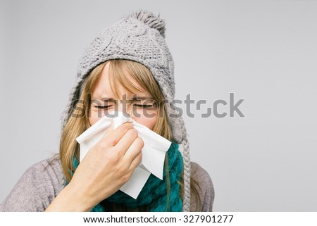 sick young woman blowing her nose isolated on light background