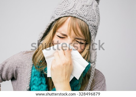 sick young woman blowing her nose isolated on light background  - stock photo