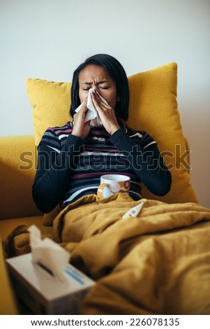 Sick young woman blowing her nose on the sofa - stock photo