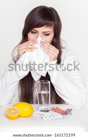 Sick young woman blowing nose - stock photo