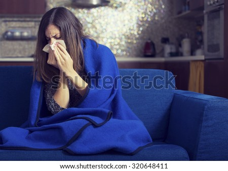 Sick young woman is coughing and blowing. - stock photo