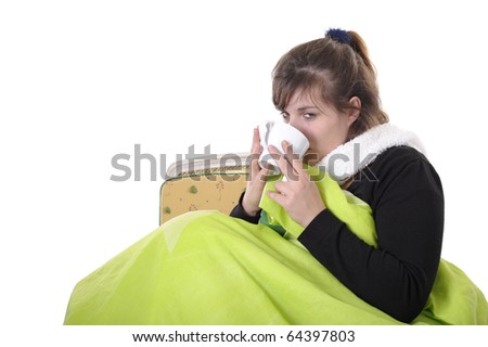 sick young woman sitting , with a hot drink, under a bedspread - stock photo