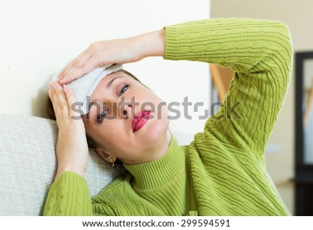 Sick young  woman with huge migraine holding wet towel on her head - stock photo