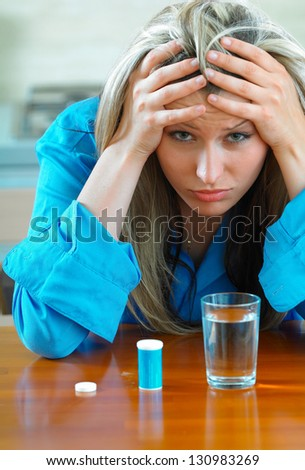 Sick young woman with pills - stock photo