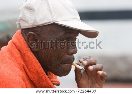 Side angle of African American man smoking outside - stock photo