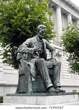 Side angle of Statue of Abe Lincoln sitting down looking downwards in Front of City Hall in San Francisco - stock photo