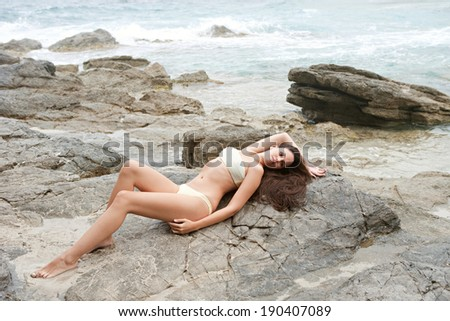 Side body view of a beautiful young woman relaxing and laying on the dark textured rocks of a beach with mountains, lounging and enjoying sunbathing on a vacation by the sea. Beauty and lifestyle. - stock photo