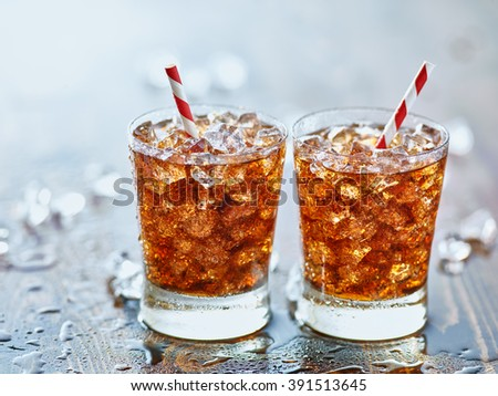 side by side glasses of ice cold cola soda pop with retro striped straws - stock photo
