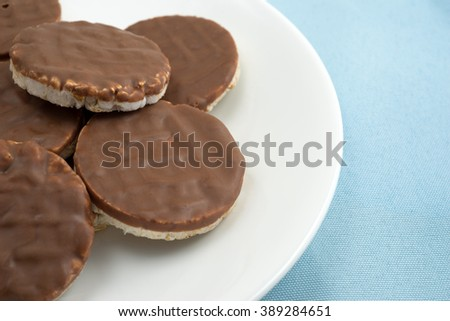 Side close view of a group of organic rice cookies with milk chocolate icing on a white plate atop a blue table cloth. - stock photo
